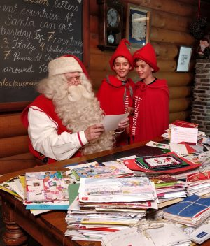 Santa Claus and twin elves in Santa Claus Main Post Office in Rovaniemi, Lapland Finland