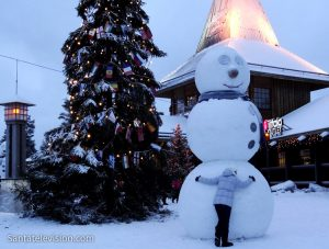 A snowman and a young traveler in Santa Claus Village in Rovaniemi, Lapland