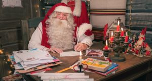 Babbo Natale che scrive un biglietto d'auguri nella Casa di Babbo Natale a Rovaniemi in Lapponia