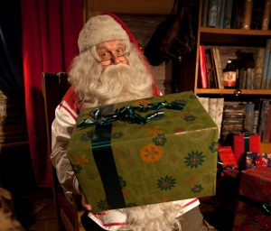 Santa Claus presenting a Christmas gift that the elves have prepared