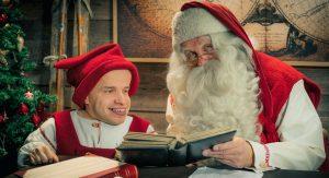 Joulupukin apulainen Kilvo-tonttu ja Joulupukki selailevat kirjaa kilteistä lapsista