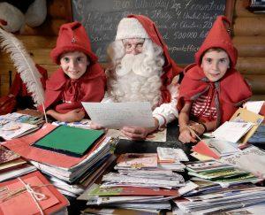Joulupukki ja kaksostontut lukevat lasten kirjeitä Joulupukin pääpostissa Rovaniemellä