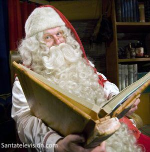 Joulupukki selailee kirjaa, johon on merkitty ovatko lapset olleet kilttejä vai tuhmia