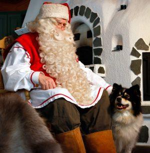 Le Père Noël et son chien de renne au coin du feu en Laponie