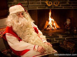 Papá Noel relajandose con la chimemea en la oficina central de correos de Santa Claus en Rovaniemi, Laponia