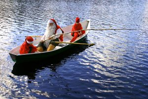 Santa Claus and his elves fishing in summer in Rovaniemi