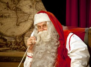 Santa Claus is making a phone call to kids around the world