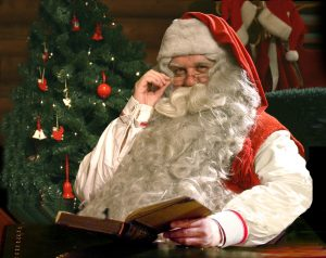 Santa Claus / Father Christmas reading a book in his house in Finnish Lapland