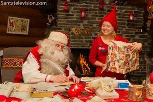 Papá Noel escribiendo cartas con la ayuda de un elfo en la oficina central de correos de Santa Claus en Rovaniemi en Finlandia
