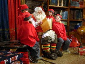 Weihnachtsmann zusammen mit seinen Elfen in seinem Büro in Rovaniemi