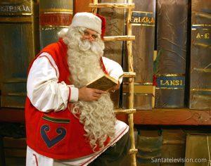 Weihnachtsmann in seinem Büro mit dem Buch über die artigen und unartigen Kinder