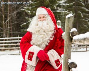 Weihnachtsmann bewundert sein Rentier auf der Rentierfarm in Lappland, Finnland