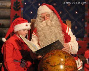 Der Weihnachtsmann und sein Elf lesen eine Karte im Haus des Weihnachtsmanns