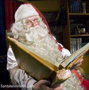 Babbo Natale che legge un libro nel Villaggio di Babbo Natale a Rovaniemi in Lapponia