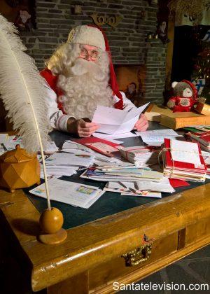 Le Père Noël lit des lettres dans son Bureau de Poste à Rovaniemi en Laponie