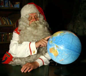 Le Père Noël regarde un globe dans son bureau en Laponie finlandaise