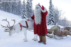 Papá Noel dando un paseo en reno por un bosque en Laponia en Finlandia