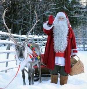 Papá Noel alimentando a uno de sus renos en Laponia finlandesa