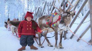 Kilvo, elfo de Papá Noel y un reno en el Pueblo de Papá Noel en Rovaniemi, Finlandia