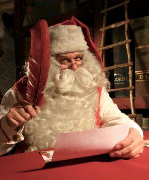 Le Père Noël écrit une carte de voeux dans son Bureau à Rovaniemi en Finlande